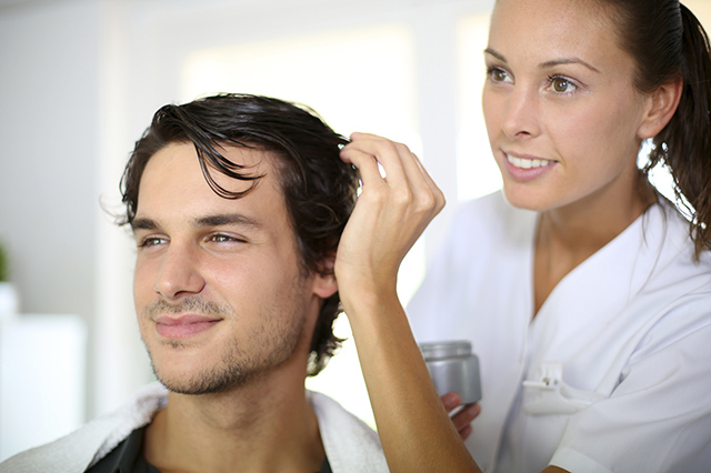 Hairdresser applying hair gel