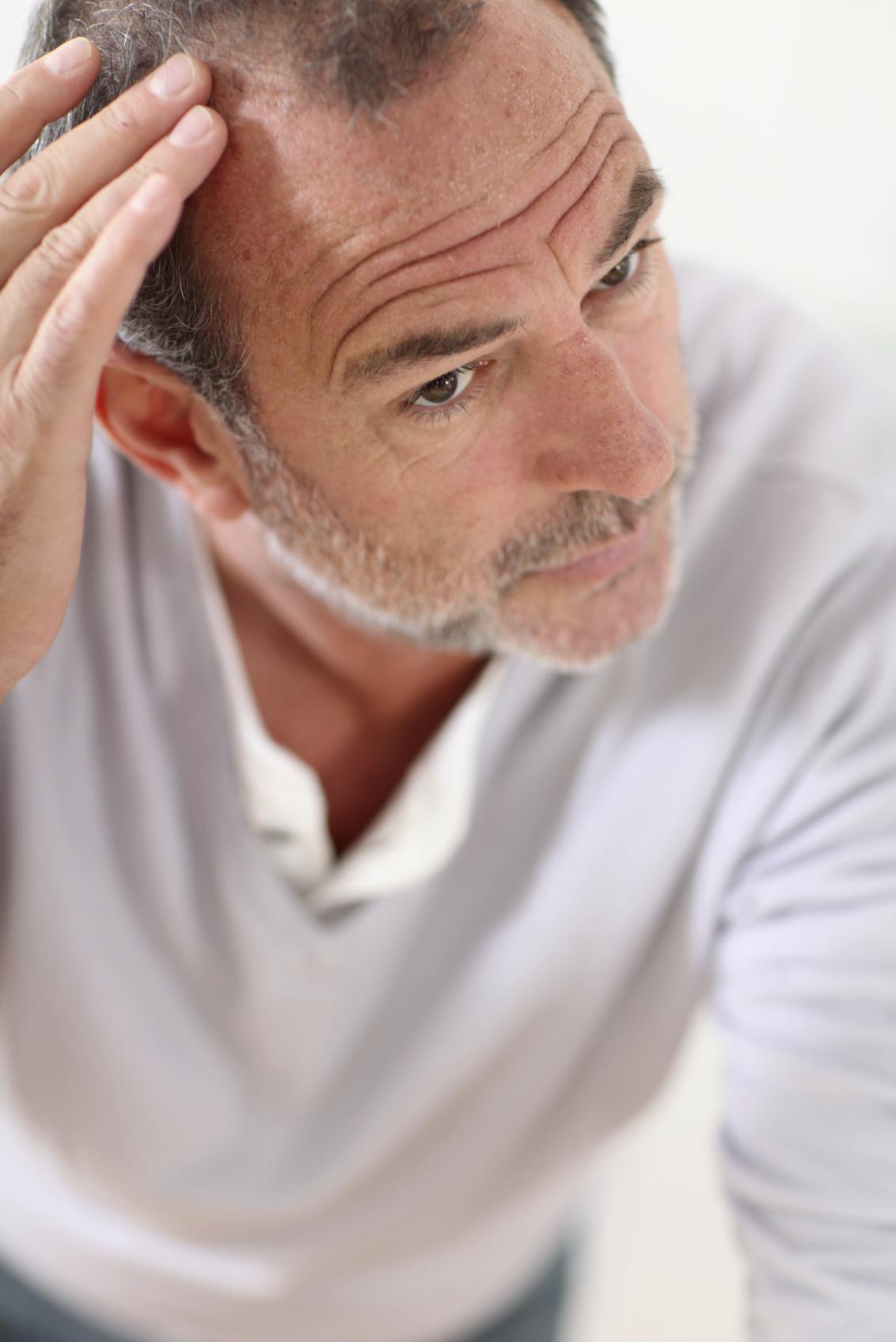 Senior man looking at his hair in mirror